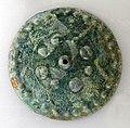 Disco in lamina con borchie e decorazioni geometriche, VII secolo ac., da necropoli di colfiorito, foligno.jpg