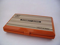 "A closed, orange dual-screen handheld device with ""Donkey Kong"" written across the top."