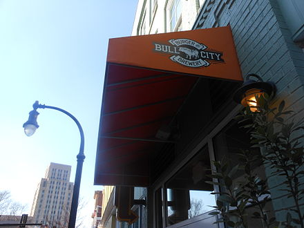 A brewery and restaurant in Downtown Durham with Hill Building in the background Durham Bar.JPG