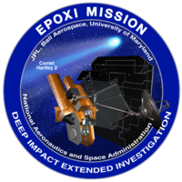 "A circle with a blue border encloses an image of a spacecraft on approach to a comet. The words ""EXPOXI Mission"" and ""Deep Impact Extended Investigation"" are written along the border of the image."