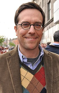 The image is of Ed Helms. He is standing outside and smiling at the camera.