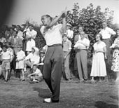 Black-and-white photograph from the front of Eric Brown which shows him finishing his golf swing over his left shoulder.