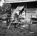 Franc Čukanja, Mihovo 11, s svedrom vrta luknje v čeljust za grablje. Zraven njega več grablšč, zadaj senene vile za seno in lesa voz 1952.jpg