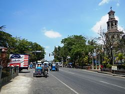 Agoo town center along the National Highway with the steeple of Basilica Minore of Our Lady of Charity on the right
