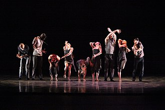 Dance - Members of an American jazz dance company perform a formal group routine in a concert dance setting