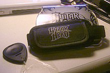 "The ""Guitar Grip"", a hand-sized unit that fits into the Nintendo DS with four colored fret buttons on one end, and an adjustable strap that the player wears to hold the Grip and DS in place while playing. The Grip features the ""Guitar Hero: On Tour"" logo on one side."