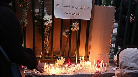"A gathering at Amirkabir University of Technology. Above flowers and lit candles a notice reads ""What is the cost of lying?"" Gathering and protest rally outside Amir Kabir University 2020-01-11 11.jpg"