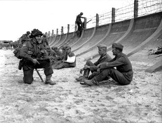 Enfilade and defilade - Juno Beach on D-Day, 1944. The barbed wire fence is crude and not very high. However, when combined with the steep, curving sea wall it slows down any attacker, giving time for the machinegun bunker (visible on the far left) to enfilade any attackers. Note the soldier in the background, forced to use a ladder