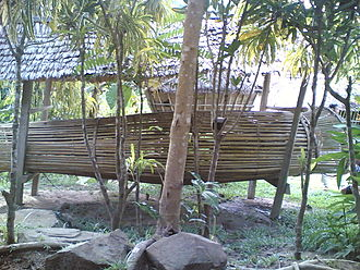 Rungus people - A large ceremonial bumbu ikan (fish trap) in a Rungus village in Kudat, Sabah in Borneo. A longhouse can be seen in the background, with distinct outward-sloped walls.