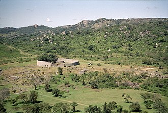Great Zimbabwe - Overview of Great Zimbabwe. The large walled construction is the Great Enclosure. Some remains of the valley complex can be seen in front of it.