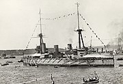 A World War I-era warship with tents erected over the fore and aft decks and flying flags from her rigging. Other warships, a small fortress and land are visible behind the ship and several small boats are visible in the foreground.