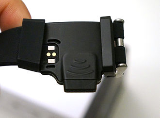 Smartwatch - HOT Watch speaker and microphone embedded on the strap. Magnetic charging pins at left.