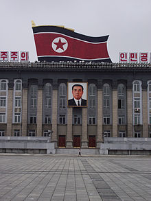 Large, columned building, with black, red and white flag and portrait of leader