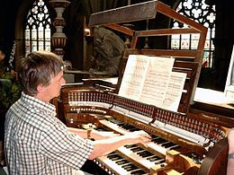 an organist seen from the right at his organ with three manuals, gothic church windows in the background