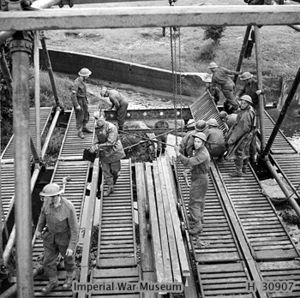A photograph showing a number of Royal Engineers sappers constructing an Inglis Bridge across a river