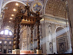 Photo shows the baldachin standing in the centre of the church, viewed looking towards the nave. There is an altar beneath it which has a red and gold frontal cloth decorated with large crosses.