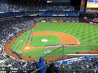 2015 National League Championship Series - The Met and Cub reserves and coaches stand on the field for introductions before Game 1 at Citi Field.