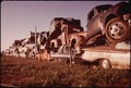 JUNKED AUTOMOBILES ARE PILED THREE DEEP ALONG FENCE - NARA - 545340.tif