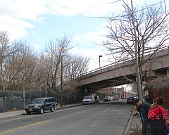 An elevated subway ramp for the BMT Jamaica Line above 130th Street in Richmond Hill, New York. The ramp descends into a tunnel portal to the left and ascends over a street to the right.