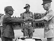 A Japanese officer hands his sword to an Australian during a surrender ceremony