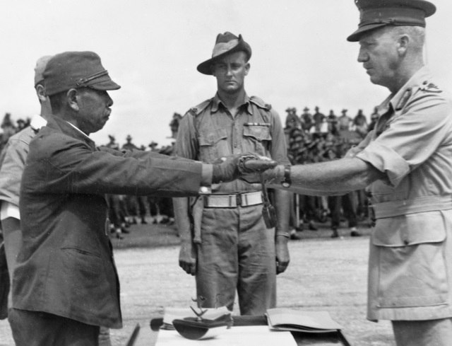 Hatazō Adachi, the commander of the Japanese 18th Army in New Guinea, surrenders his sword to the commander of the Australian 6th Division, Horace Robertson.