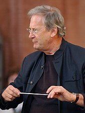 a conductor in profile, looking at (unvisble) performers, with the baton horizontally between his hands, as if waiting for enough silence to begin
