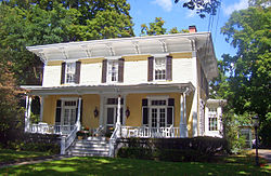 A yellow house partially in sunlight with wide roof eaves and a front porch