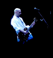 A man in a white shirt playing guitar on stage