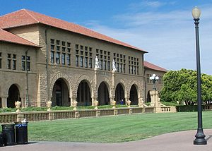 Main Quad (Stanford University) - Jordan Hall (building 420) named after the university's first president.  Note the white statues of Agassiz and Humboldt over the arches and in the front part of the sandstone balustrade with its urns.