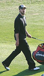 A brunette man with facial hair walks over grass holding a golf club.