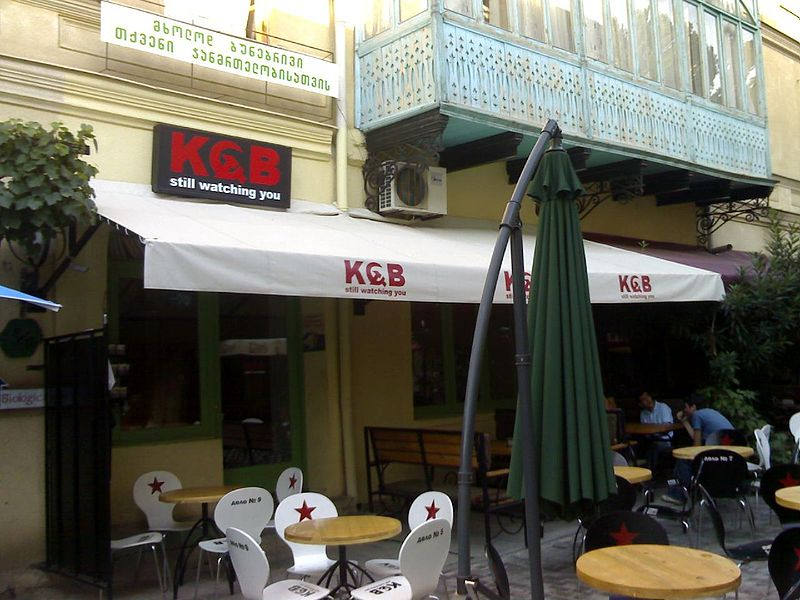 """File:KGB - Still Watching You.jpg - cafe with KGB logos and """"KGB still watching you"""" sign above the awning."""