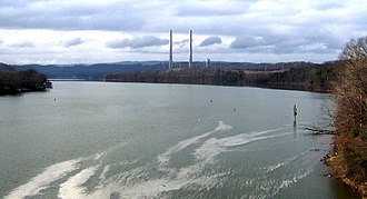 Kingston Fossil Plant coal fly ash slurry spill - The confluence of the Clinch and Emory Rivers, with the Kingston Fossil Plant in the distance, five days after the spill. The white foam floating on the water consists of cenospheres, which are a component of the ash.
