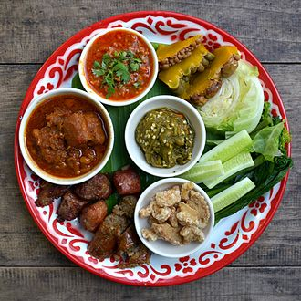 Pork rind - Khaep mu (in the bowl at the bottom of the image) served as one of the starters in this selection of northern Thai dishes