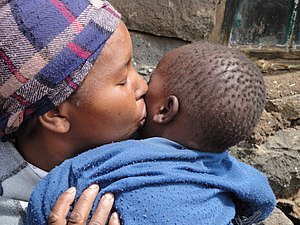 HIV/AIDS in Lesotho - A Bathoso woman kisses her son, who was born HIV-free in 2008 due to successful PMTCT treatment at Molikaliko health clinic, Lesotho.