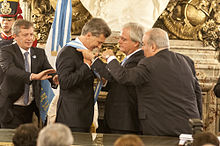 A smiling Macri puts on a blue-and-white sash with the help of Federico Pinedo and two other men