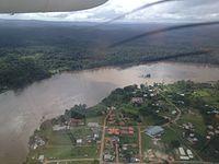 photographie prise d'un avion. La forêt à perte de vue, la rivière qui fait un méandre, un quartier urbain avec quelques maisons individuelles