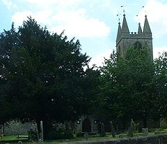 Top of ower with spirelets seen behind trees. In the foreground is grass and gravestones