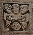 Marmoutier, Romanesque relief, six heads and two legs.jpg