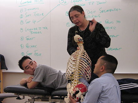 A physician demonstrates an OMT technique to medical students at an osteopathic medical school. Medical School.jpg
