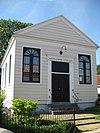 foto van Vermaning, doopsgezinde houten zaalkerk met boogramen, omlijste ingang en frontonvormige gevelbekroning, met ernaast wijkgebouw