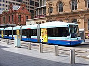 Two-tone blue tram with doors open