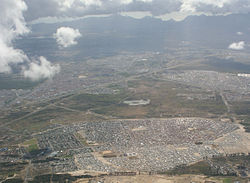 An aerial photograph of Mfuleni in the foreground stretching to the west towards Table Mountain. Ikweze Park (on the left) and Delft (to the right) are situated beyond.