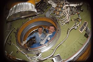 Mikhail Tyurin - Mikhail Tyurin (right) and Michael E. Lopez-Alegria conduct pre-spacewalk operations in the Pirs Docking Compartment