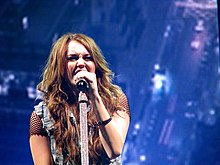 A teenage female with long, brunette hair, a fishnet shirt and a jean vest sings into a microphone. Behind her, images of a cityscape are projected.