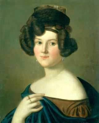 The head and upper torso of a young white woman with dark hair done in an elaborate style. She wears a small hat, a cloak and dress that expose her shoulders and pearl earrings. On her left hand that holds the edge of the cloak, two rings are visible.