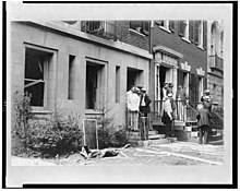 Black and white photo of people in front of a damaged house