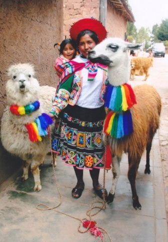 Mother and child with two alpacas in Peru