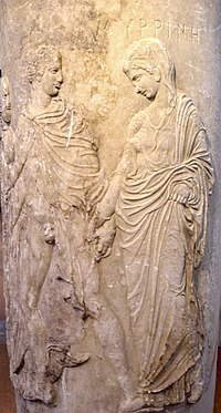 A carving of a noble robed man and woman apparently leading a demure, robed woman. The man's robe is open, exposing his penis. He holds the hand of the woman.