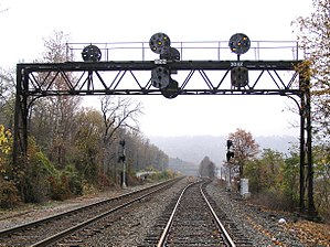 North American railroad signals - A Pennsylvania Railroad position light signal bridge with replacement mast signals in the background. The design of steam locomotives meant that all signals had to be placed to the right of the running track. Current diesel engine design allows both left- and right-hand siting.