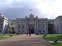 Facade of an ornate 18th century building, with tall stone columns, a wide arched entrance, balustraded roof and a central pediment from which a flag is flying. The building is approached by a wide path flanked by lawns.
